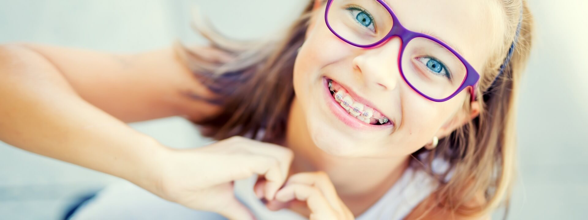 smiling-little-girl-with-dental-braces-and-glasses-showing-heart-with-picture-id842727584